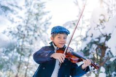 Winter fairy tale. Cute boy violinist in winter forest. stock images