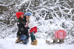 A winter fairy tale, a young mother and her daughter ride a sled Stock Images