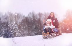 A winter fairy tale, a young mother and her daughter ride a sled Stock Photos