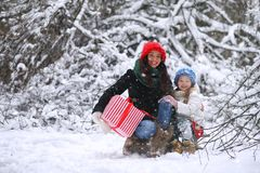 A winter fairy tale, a young mother and her daughter ride a sled Stock Image
