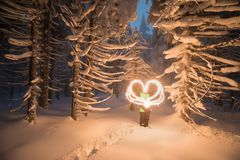 Winter fairytale, heavy snowfall covered the trees and houses in the mountain village. girl flare draws heart stock photos