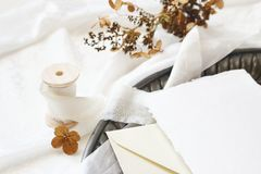 Winter, fall wedding, birthday table composition. Stationery mockup scene. Greeting card, envelope, dry hydrangea. Flowers and silk ribbon on old vintage tray stock images