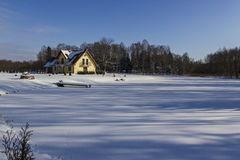 Winter family lake house. The family house on the frozen lake, with a garden and a bridge Stock Photo