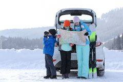 Young woman with her children on snowy road stock photography