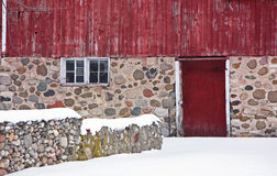Winter on the Farm. Closeup of weathered red barn with stone foundation in winter Stock Photos
