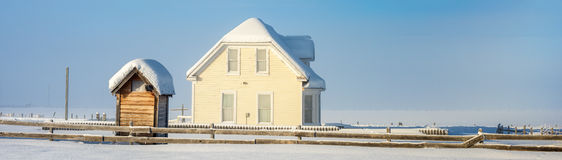 Winter farm house in Idaho with fence. Outhouse and ranchhouse in winter blanketed with snow Stock Photo
