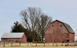 Winter Farm Scene. This is a Winter picture of a family farm barn and outbuilding with tree skeletons in the background located in Madison County, Illinois Stock Photography