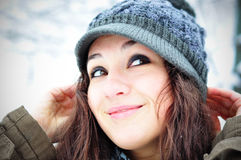 Winter fashion. Close-up portrait of a beautiful young woman smiling outside in winter time Royalty Free Stock Images