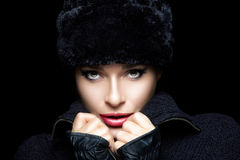 Winter Fashion. Beautiful Young Woman in Fur Hat and Mittens Royalty Free Stock Photography