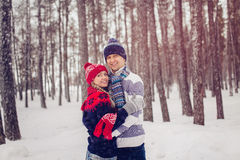 Winter, fashion, couple concept - smiling man and woman in hats and scarf hugging over forest background stock image