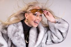 Winter Fashion Girl. Close up of an attractive blond girl in a faux-fur coat wearing sunglasses Stock Photography