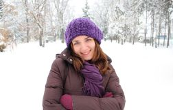 Healthy young woman wearing purple hat and winter clothes, smiling, in a park covered with snow Royalty Free Stock Images