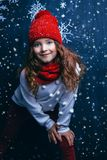 Winter fashion for kids. A portrait of a pretty young girl wearing a hat, a sweater and a scarf. Winter fashion for kids, beauty stock photography