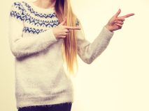 Woman legs in black trousers and furry jumper. Winter fashion, outfit ideas concept. Woman legs in black leggings trousers and grey furry jumper pointing right Stock Photography