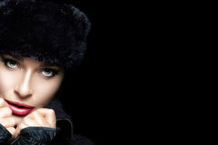 Winter Fashion Portrait. Beautiful Young Woman Face in Fur Hat. Winter Beauty. Fashion beautiful girl with trendy fur hat and mittens. High fashion portrait with stock images