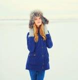 Winter fashion portrait smiling woman wearing fur hat over snow. Winter fashion portrait smiling woman wearing a fur hat over snow Stock Photography