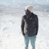 Winter fashion portrait stylish young african man wearing a sunglasses, knitted hat and jacket over snow Royalty Free Stock Photography