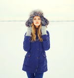 Winter fashion portrait young woman wearing fur hat over snow field. Winter fashion portrait young woman wearing a fur hat over snow field Royalty Free Stock Images