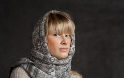 Winter fashion shot of a beautiful girl with long. Curled blonde hair wearing a grey woolen cap and grey sweater. This image has attached release Royalty Free Stock Photos