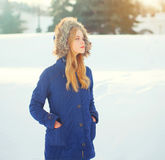 Winter fashion woman wearing jacket with hood on head over snow. Winter fashion woman wearing a jacket with hood on head over snow Stock Image