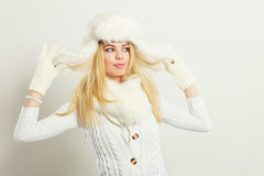 Woman wearing fashionable wintertime clothes. Winter fashion. Young blonde woman wearing fashionable wintertime clothes white fur scarf cap, woolen gloves Royalty Free Stock Photography