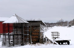Winter feed. Two corn cribs, one empty and the other full, in snowscape Royalty Free Stock Images