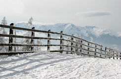 Winter fence. Wooden fence in winter alpine scenery Stock Photography