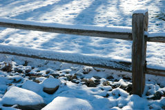 Winter Fence. Snow on a rail fence with tree shadow Royalty Free Stock Photography