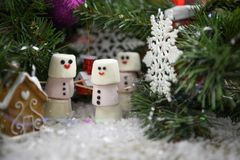 Christmas food photography picture of marshmallows in shape of snowman in snow under a Christmas tree with decorations. Winter festive Christmas or New Year Stock Photography