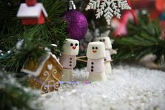 Christmas food photography of marshmallows in snowman shapes under a Christmas tree with decorations and warm cosy background Stock Photos