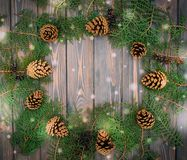 Winter festive decorations. Christmas card with fir cones and wooden background Royalty Free Stock Photography