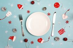 Winter festive table setting with cutlery and Christmas decorati. Ons on blue table. Top view. Christmas tableware Royalty Free Stock Images