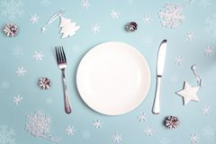 Winter festive table setting with cutlery and white decorations. On blue table. Top view. Christmas tableware Stock Photos
