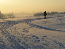 Winter field and walking man. The image of a winter field, river and  walking man Royalty Free Stock Photos