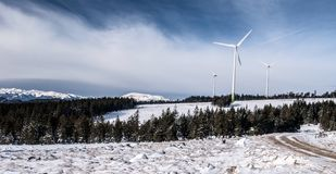 Winter Fischbacher Alpen mountain range in Austria with wind turbines and higher peaks on the background. Winter Fischbacher Alpen mountain range in Austria with royalty free stock image