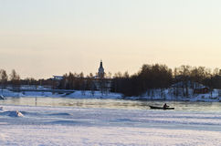 Winter fishing. Lonely fisherman rows his boat in mid-january in Oulu-river, northern Finland. The characteristic Oulu cathedral is visible in the background royalty free stock photo