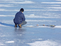 Winter fishing. Man fishing at frozen lake. Ice drill visible. Smudges of snow Royalty Free Stock Photos