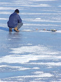 Winter fishing. Man fishing at frozen lake. Ice drill visible. Smudges of snow Royalty Free Stock Photo
