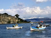 Winter fishing boats. Winter scene of fishing boats with the snow covered mountains of Evia in the background Stock Image