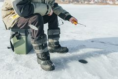 Winter fishing, fishing rod stands on the hole waiting for the fish. To bite Stock Photography