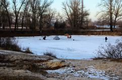 Winter fishing on a frozen river stock images