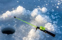 Winter fishing hole and fishing rod stock photo