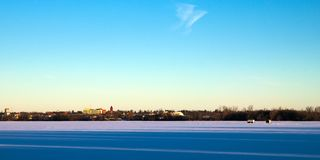 Winter Fishing Houses on frozen Lake Irving in Bemidji, Minnesota. On a clear December morning with the city of Bemidji, in background and long shadows in stock photo