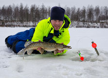 Winter fishing lucky day. Happy angler with winter pike trophy fish Royalty Free Stock Images