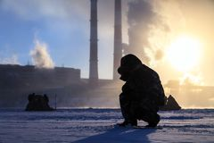 Winter fishing, men`s passion, fishermen catch fish on a frozen river against the background of the factory pipes at sunset. stock images