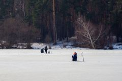 Winter fishing. River, lake near forest in ice. Anglers, Fishermens during your favorite leisure time. Copy space, for. Winter fishing. River, lake near forest Stock Photography