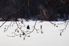 Winter fishing. River, lake near forest in ice. Blurred image of Anglers, Fishermens through tree branches, favorite men. Winter fishing. River, lake near forest Royalty Free Stock Photos