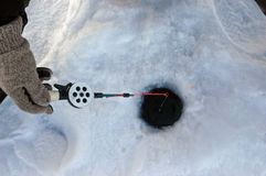 Winter fishing tackle. Fisherman holding a winter fishing tackle on the stood Krasnoyarsk water basin Stock Photos