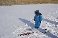 Winter fishing Young fisherman Stock Image