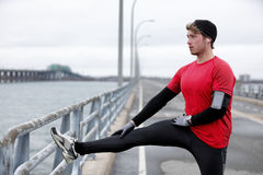 Winter fitness running man warm-up stretching legs royalty free stock photo